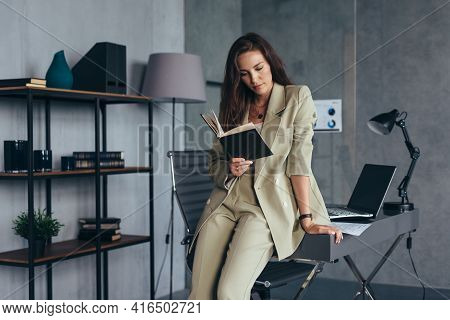 Businesswoman In The Office Stands At Her Desk And Reads Her Notebook.