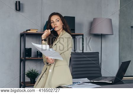 Woman Stands Thoughtfully With Her Papers Leaning On Her Desk