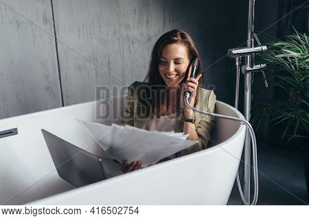 Woman Sits In The Bathtub And Speaks Jokingly Into The Shower Head As If On The Phone