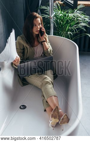 Woman Sits In The Bathtub With Her Laptop And Calls