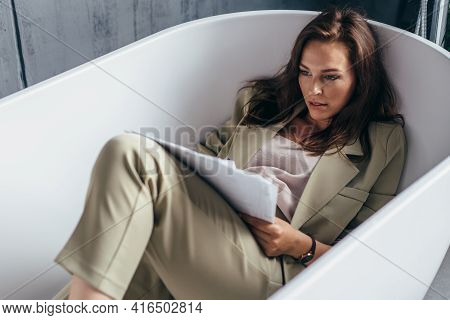 Woman Does Paperwork While Sitting In The Bathtub