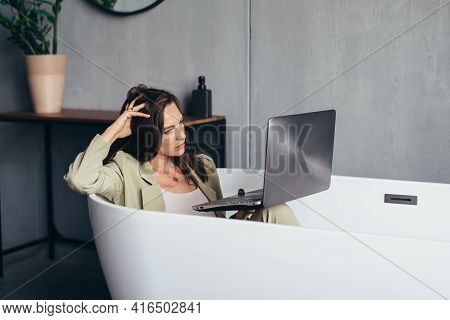 Woman Works In The Bathtub With Her Laptop In The Privacy Of Her Home