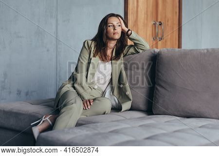 Woman In The Suit Sits On The Couch Thoughtfully