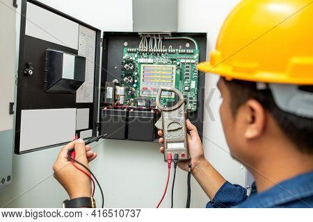 Electrician Working Use Digital Clamp Meter In Hands Of Electrician, Close-up Against Background Of