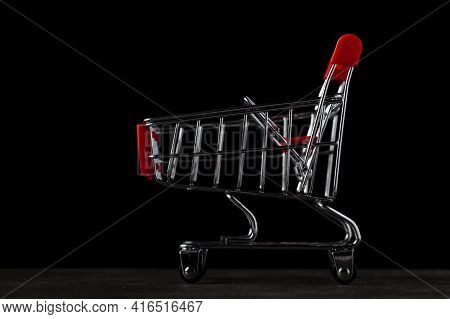 Dark Background Image With An Empty Toy Shopping Cart.  A Concept Image For Economic Downturn, Reces