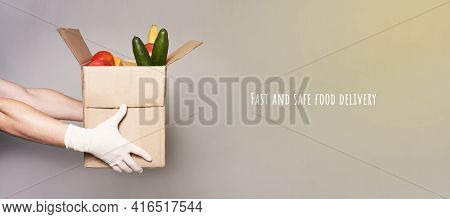 A Courier Hands In Gloves. Man With Cardboard Box Of Groceries, Fast And Safe Food Delivery.delivery