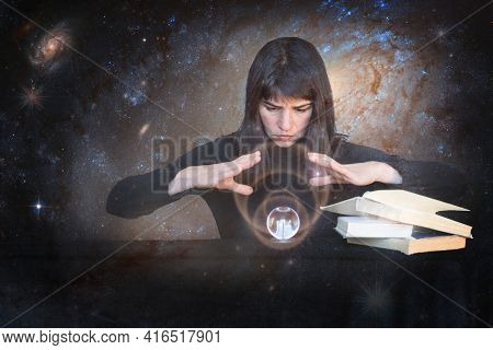 The Girl Holds Her Hands Over A Shining Ball And Looks To The Future Next To Magic Books On The Back