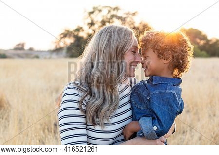 Beautiful happy Mother holding her adorable diverse son in the outdoor sunlight. Sun rays shining through as the mom shows love and affection to her son