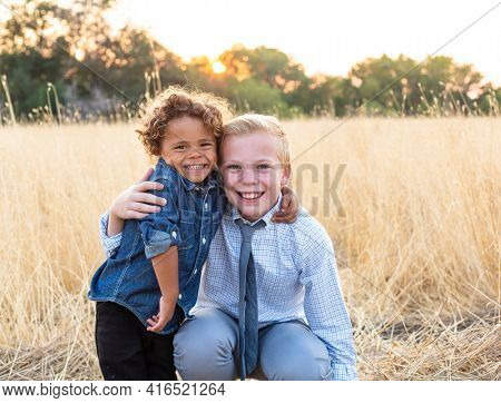 Portrait of two happy diverse little boys outdoors in a grassy field. Hugging each other in love and friendship.