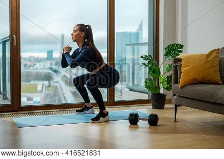 Slim brunette woman in green tracksuit with brown ponytail practices squat position by panoramic window on glazed balcony