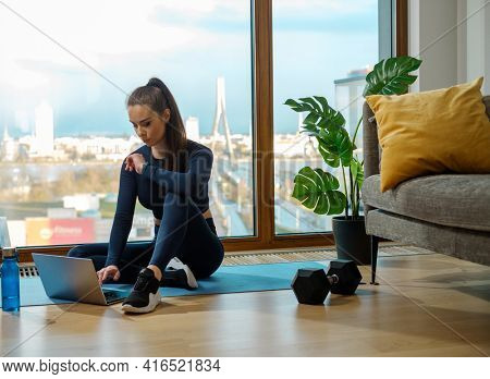 Brunette with ponytail in green tracksuit browses web on laptop sitting on blue mat near panoramic window and pot plant in lodge