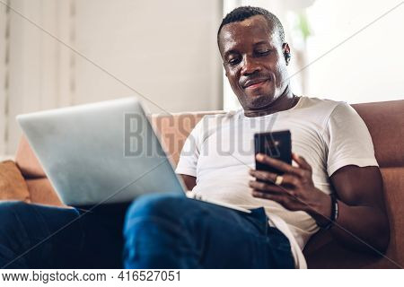 Young Black African Man Relaxing Using Laptop Computer Working And Video Conference Meeting At Home.