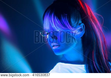 Neon Woman dancing. Fashion model girl in neon light, portrait of beautiful model with fluorescent make-up, Night club. Disco dancer posing in UV, colorful make up. On bright background