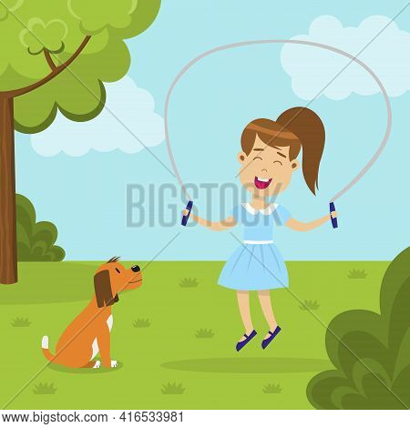 Cute Smiling Girl Jumping Rope In The Park And A Dog Looking At Her. Happy Jumping Kid With A Pet. C