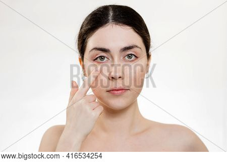 Eye Health. Portrait Of A Woman Pointing Her Finger At The Eye. White Background. Copy Space. Vision