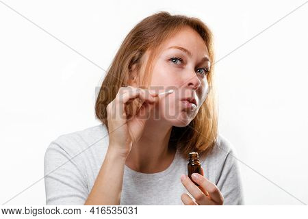 Portrait Of A Young Woman Smearing Medicine On A Pimple On Her Face. White Background. Acne And Pimp
