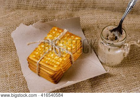 Rectangular Crackers And A Glass Jar Of Liver Pate On Sackcloth. A Stack Of Crispy Saltine Crackers