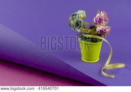 Yellow Metal Bucket With A Bouquet On A Two-color Abstract Geometric Background. A Bucket With Artif
