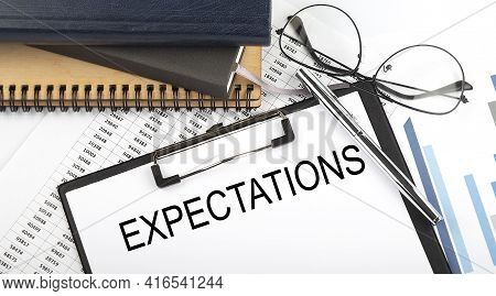 Text Expectations On Office Desk Table With Notebooks, Supplies,analysis Chart, On The White Backgro