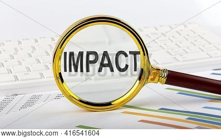 Magnifying Glass With The Word Impact On The Chart Background