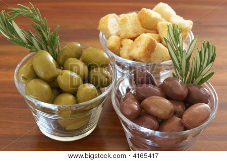 Two Jars Of Green And Black Olives And Croutons