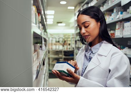 Young Female Pharmacist Reading Instructions On Medicine Box Standing In Aisle Of Chemist