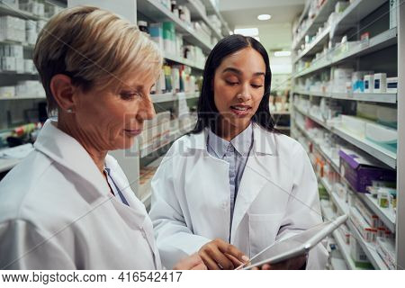 Two Female Pharmacists Discussing In Chemist Using Digital Table While Standing Between Aisle