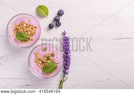Bowls Of Berries Yogurt With Granola And Oats For Healthy Breakfast On A Rustic White Table Backgrou