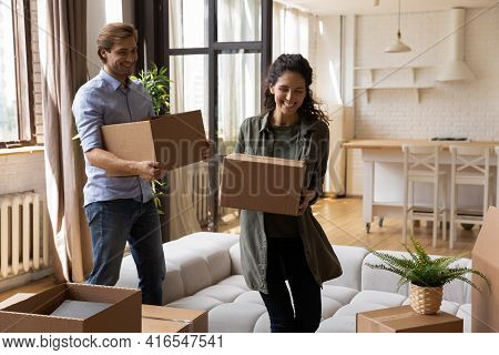 Overjoyed Family Carrying Cardboard Boxes, Relocating To New Apartment