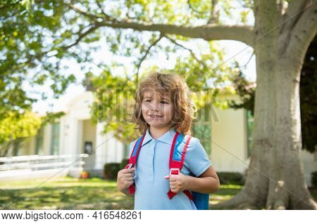 Child With Rucksacks Standing In The Park Near School. Pupils With Books And Backpacks Outdoors. Kid