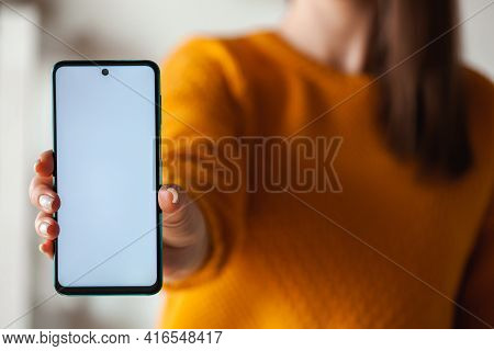 Woman Hold Mobile Phone Screen Mockup In Hands In Orange Sweater