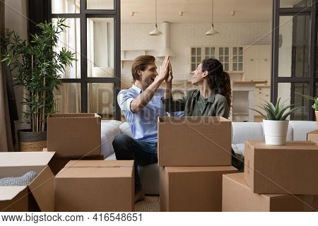 Overjoyed Young Couple Celebrating Relocation, Unpacking Boxes, Giving High Five