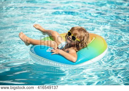 Summer Vacation. Summertime Kids Weekend. Boy In Swiming Pool. Funny Boy On Inflatable Rubber Circle