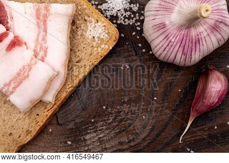 Pieces Of Salted Lard On Bread, A Head Of Garlic And Salt On A Wooden Cutting Board. Sandwich With L