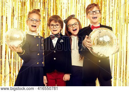 Kid's fashion and holidays. Happy children in evening dresses cheerfully shout, holding disco balls in their hands on  shiny gold foil curtains background. Children's party.