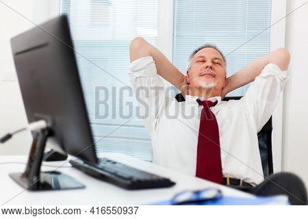 Businessman relaxing in swivel chair in office