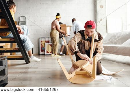 Young furniture assemblage specialist in workwear standing on knees on the floor and assembling new wooden chair against settlers