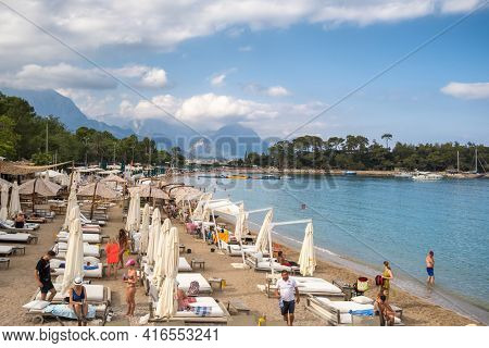 Kemer, Turkey - October 14, 2020: Deck chairs on the beach with umbrellas and loungers with mountains at background in Kemer, Antalya, Turkey