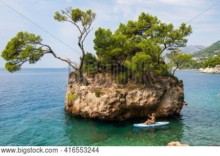Makarska, Croatia - September 6, 2019: Unidentified woman riding sea kayak near croatian coast of Adriatic Sea in Makarska Riviera, Dalmatia, Croatia.