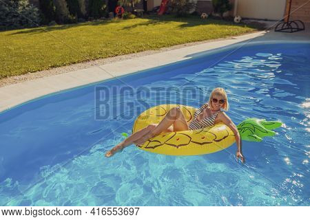 Attractive Young Woman Wearing Swimsuit Floating On Swimming Float, Enjoying Sunny Summer Day At The