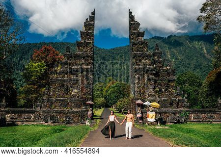 Beautiful couple at the Bali temple. Man and woman traveling in Indonesia. Couple at the Bali gate. The couple travels the world. Tourists in Bali. Travel to tourist places in Asia. Copy space