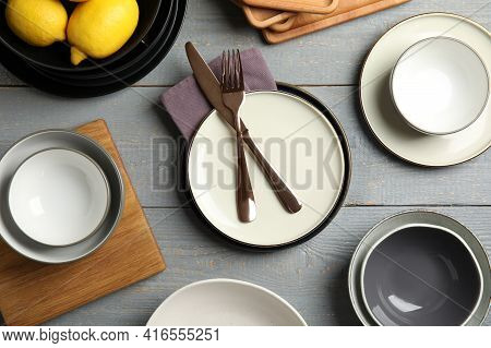 Set Of Clean Dishware And Lemons On Grey Wooden Table, Flat Lay