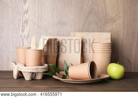 Set Of Disposable Eco Friendly Dishware And Apple On Wooden Table