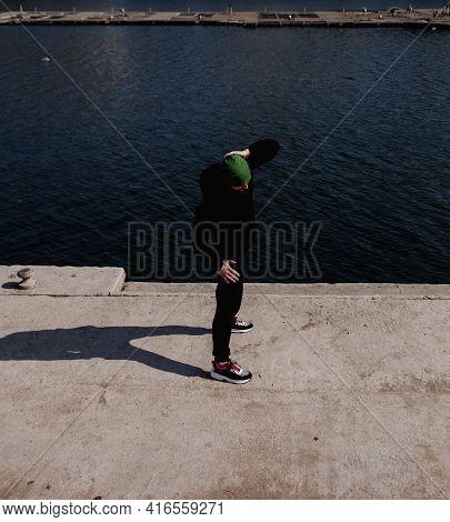 Sportsman In Black Sportswear Doing Exercises In Park On River Background