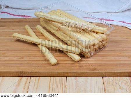 Breadsticks With Sesame Seeds, Wheat Ear In Transparent Plastic Container On A Wooden Board On Rusti