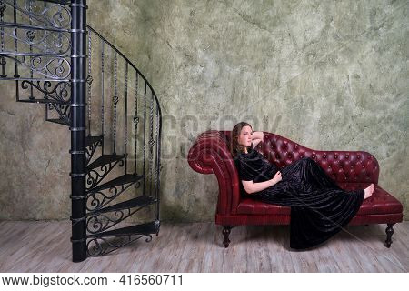 A Pregnant Woman In An Evening Dress Is Lying On A Red Sofa By The Old Spiral Staircase. Retro Full-