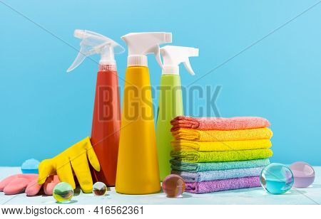 Colored supplies for cleaning on blue background.Spray Bottles of detergent, rubber protective gloves and rags rainbow colors. Concept of spring cleaning home.