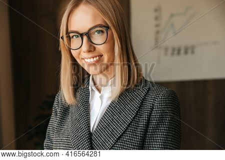 Portrait Of A Business Woman In Glasses, In A Strict Business Suit, Smiling With Teeth In The Office