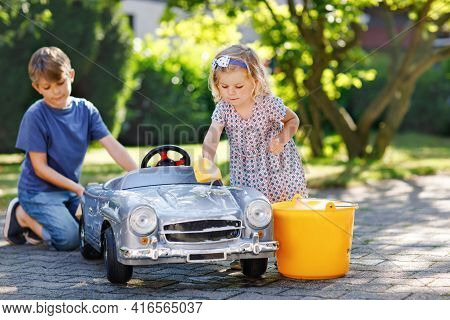 Two Happy Children Washing Big Old Toy Car In Summer Garden, Outdoors. Brother Boy And Little Sister