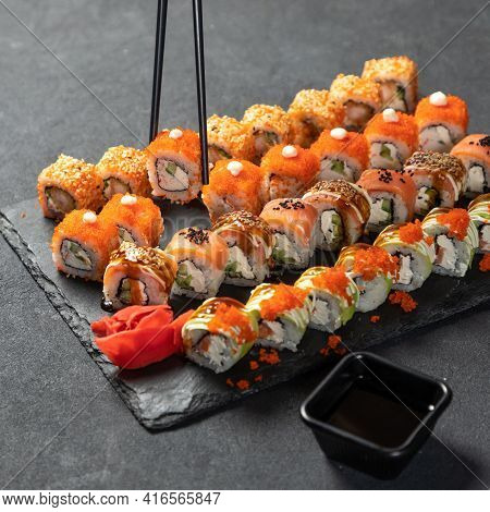 Holding Sushi With Chopstick. Feng Shui Roll, Kani Hot Sushi Roll With Philadelphia Roll Close Up